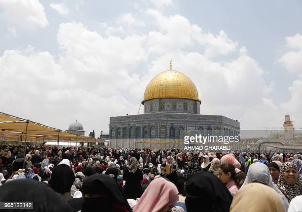 Palestinian worshippers pray outside the Dome of the Rock in Jerusalem's AlAqsa Mosque compound on the third Friday prayers of the Muslim holy month...