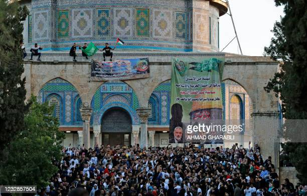 Palestinian worshippers raise the Hamas and the Palestinian flag along with a Hamas poster with portraits of its leaders, at the Dome of the Rock...