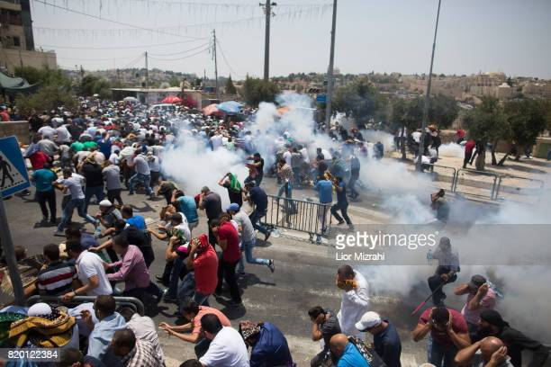 Palestinian worshippers run for cover from teargas fired by Israeli forces following prayers in Ras elAmud Area outside the Old City on July 21 2017...
