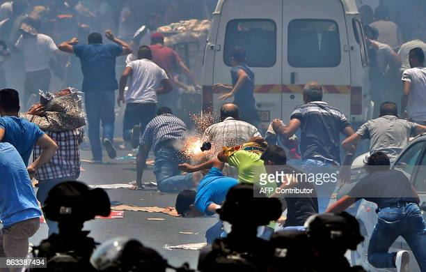 TOPSHOT Palestinian worshippers run for cover from teargas fired by Israeli forces following prayers outside Jerusalem's Old City in front of the...