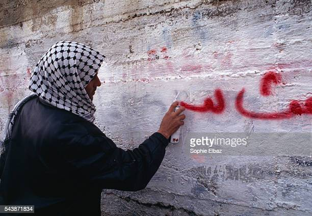 A Palestinian writes graffiti on a wall in Hebron Violence erupts in the wake of the Hebron massacre which killed 52 Palestinians
