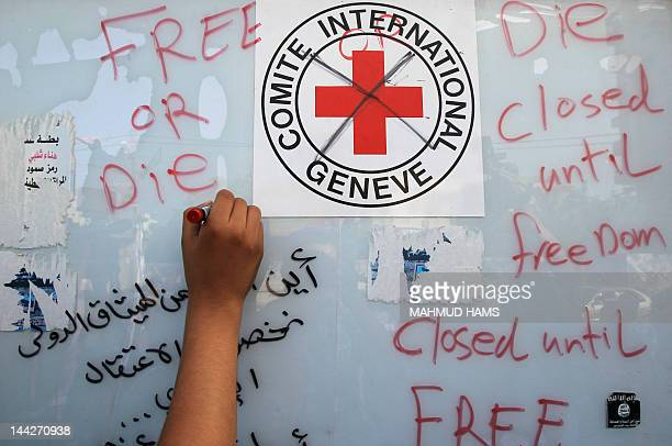 A Palestinian writes outside the headquarters of the International Committee of the Red Cross in Gaza as protestors forced the offices to close for...