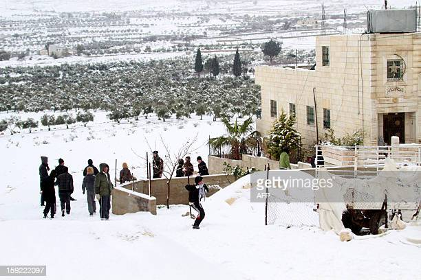 Palestinian youngs play with snow balls after heavy snow falls on January 10 2013 in Tuqua near the West Bank City of Bethlehem Abnormal storms which...