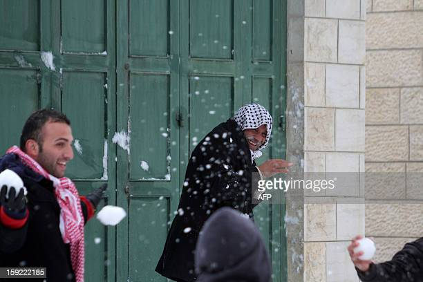 Palestinian youngs play with snow balls in front of an elderly man smiling after heavy snow falls on January 10, 2013 in Tuqua, near the West Bank...