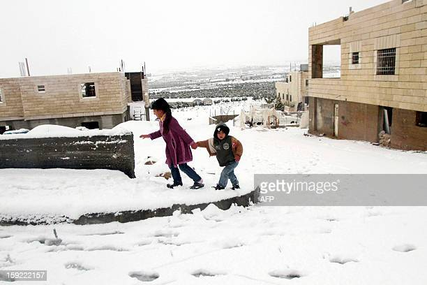 Palestinian youngs walk on a snowcovered street after heavy snow falls on January 10 2013 in Tuqua near the West Bank City of Bethlehem Abnormal...