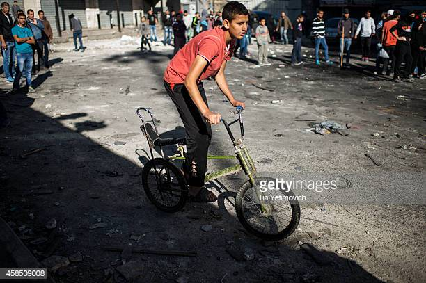 Palestinian youngster seen riding a bicycle as palestinian youth clash with police at Shuafat refugee camp a day after a Palestinian resident of the...