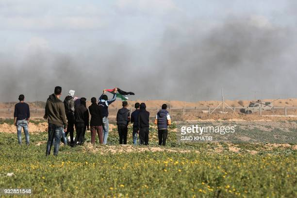 Palestinian youngsters demonstrate near Khan Yunis by the border fence between Israel and the southern Gaza Strip on March 16 2018 / AFP PHOTO / SAID...