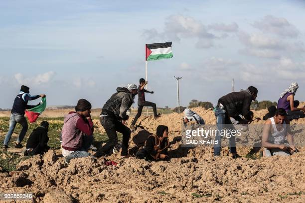 Palestinian youngsters hide and hold Palestinian flags as they demonstrate near Khan Yunis by the border fence between Israel and the southern Gaza...