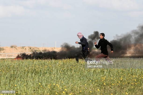 Palestinian youngsters run as they demonstrate near Khan Yunis by the border fence between Israel and the southern Gaza Strip on March 16 2018 / AFP...
