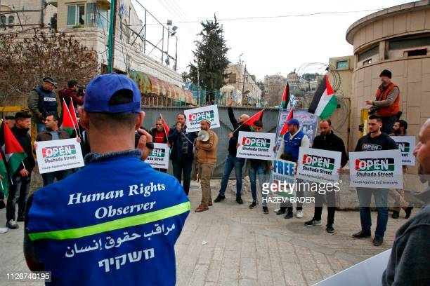 A Palestinian Youth Against Settlements organisation volunteer stands in front of protesters demanding the reopeneing of Hebron's main alShuhada...