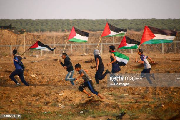 Palestinian youth are seen flying Palestine flags during the protest Demonstration between the Israeli soldiers and Palestinian citizens during a...