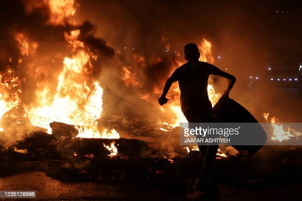 Palestinian youth carries a tyre before setting it ablaze, during confrontations with Israeli security forces following a rally in support of...