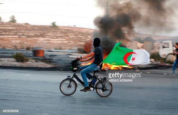 A Palestinian youth carries an Algerian flag as he rides a bicycle during clashes between Palestinian protesters and Israeli security forces near the...