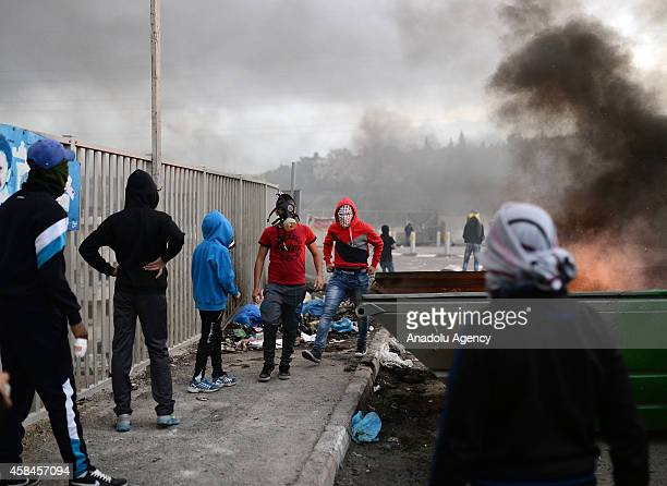 Palestinian youth clash with Israeli police at Shuafat refugee camp after a Palestinian rammed his vehicle into a crowd of pedestrians in Jerusalem...