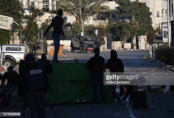 TOPSHOT Palestinian youth confront Israeli troops with stones after a house belonging to a Palestinian accused of killing an Israeli soldier a few...