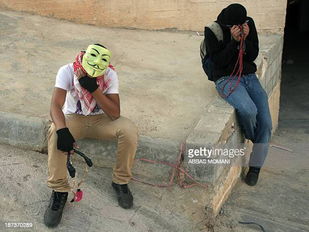 Palestinian youth cover their eyes after being caught in tear gas during clashes with Israeli soldiers close to the Israeli Ofer military prison near...