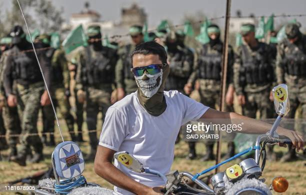 Palestinian youth covering his face with a mask rides his motorbike in front of fighters from the Ezzedin alQassam Brigades the armed wing of the...