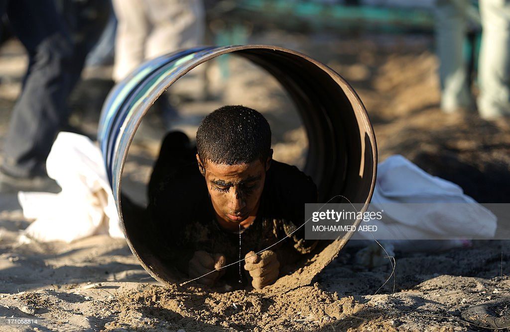 A Palestinian youth crawls through a tunnel during a summer physical training camp run by Hamas in Gaza City on June 21, 2013.