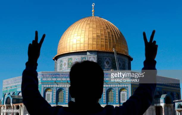 Palestinian youth flashes the Vsign for victory during Friday prayers in front of the Dome of the Rock mosque at the AlAqsa mosque compound in...