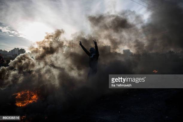 Palestinian youth gestures in the smoke of a tire fire as they clash with Israeli Defence Forces in the streets on December 11 2017 in North of...