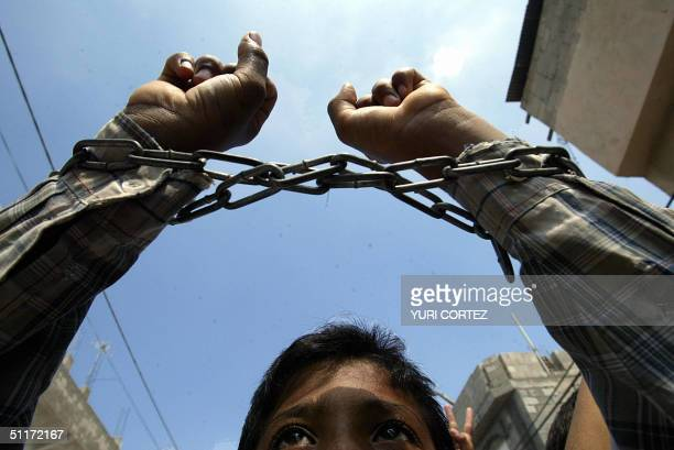 Palestinian youth his hands chained in a symbolic gesture takes part in a rally 15 August 2004 in Beit Hanun in the Gaza Strip in support of...
