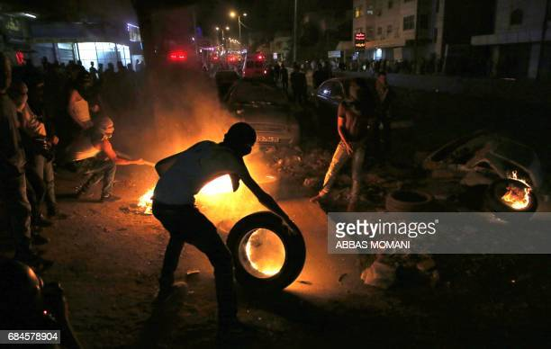 Palestinian youth holds a burning tyre during clashes with Israeli soldiers at the Qalandiya checkpoint near the West Bank city of Ramallah following...