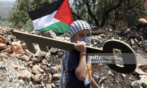 Palestinian youth holds a cutout symbolising the key to houses left by Palestinians in 1948 as Palestinian protesters clash with Israeli forces...