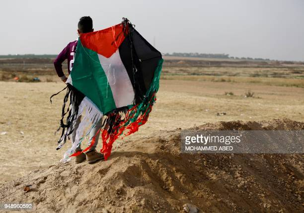 Palestinian youth holds a kite with the colours of his national flag at the site of protest tents next to the Gaza Strip's border fence with Israel...