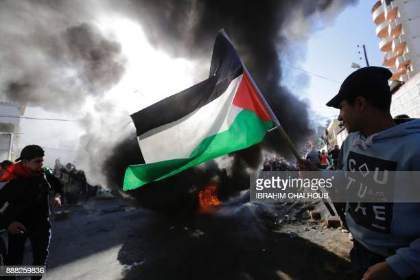 Palestinian youth holds a national flag during a protest in the refugee camp of Beddawi on the outskirts of the northern Lebanese port city of...