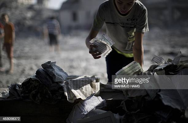 A Palestinian youth holds pages of destroyed copies of the Koran Islam's holy book on August 2 2014 after a mosque was hit in an overnight Israeli...