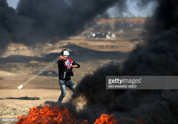 Palestinian youth hurls a stone during clashes with Israeli forces on May 15, 2018 near the border fence with Israel east of Jabalia in the central...