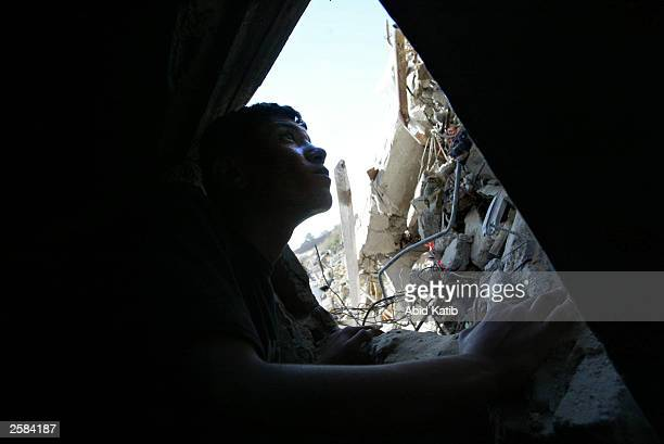 Palestinian youth inspects the rubble of his destroyed house October 12, 2003 in Rafah Refugee Camp, Gaza Strip. Many homes were demolished during...