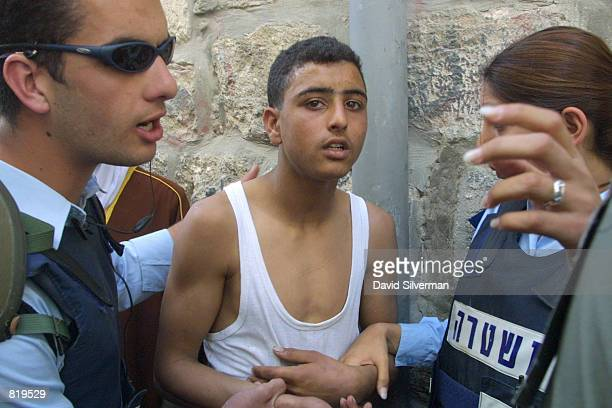 Palestinian youth is arrested by Israeli police on suspicion of throwing stones during clashes in Jerusalem's Old City March 30 2001 in Jerusalem...