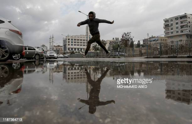 A Palestinian youth jumps over a water puddle following a rainstorm in Gaza City on December 9 2019