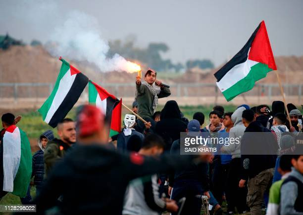 Palestinian youth lights up a flare as he is being carried on the shoulders of a man waving Palestinian flags together during a demonstration along...