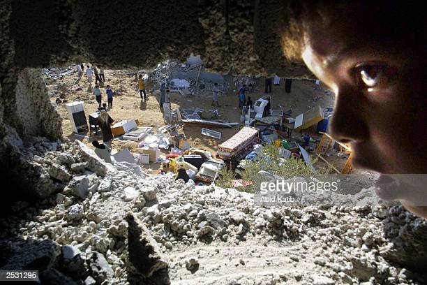 Palestinian youth looks out of a hole in a house after clashes between Israeli forces and Palestinian militants September 24 2003 in the Rafah...