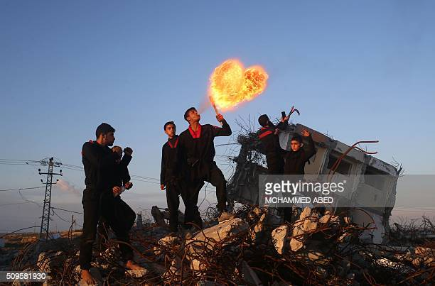 TOPSHOT Palestinian youth members of a Gazan martial art group perform fire breathing at ruins of a house that was destroyed in the 2014 war between...