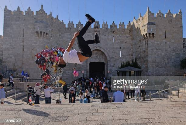 Palestinian youth performs a jump outside the Damascus Gate in Jerusalem's Old City on May 13, 2021 during Eid al-Fitr, which marks the end of the...