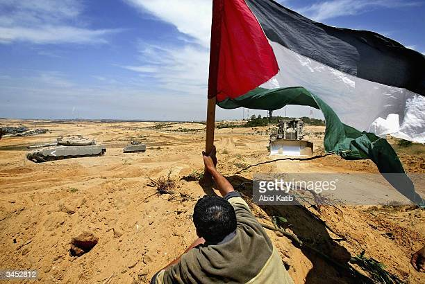 Palestinian youth plants a Palestinian flag near an Israeli tank and bulldozer during clashes with Israeli soldiers April 20 2004 near the Beit...