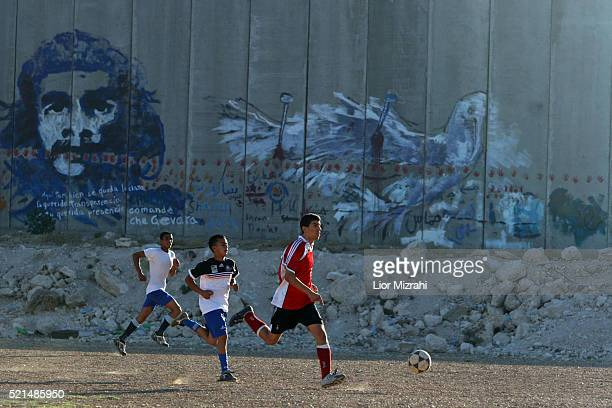 Palestinian youth play football next to a section of Israel's separation barrier in the west bank village of Abu Dis in the outskirts of Jerusalem...