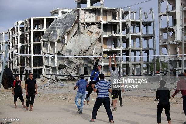 Palestinian youth play volleyball on May 5 2015 in front of bulldings that were destroyed during the 50day war between Israel and Hamas militants in...