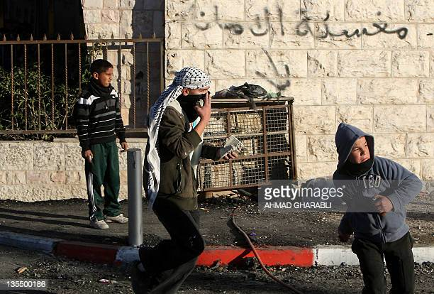 Palestinian youth prepare to throw stones towards Israeli border guards during a protest against the construction of a new Israeli checkpoint near...