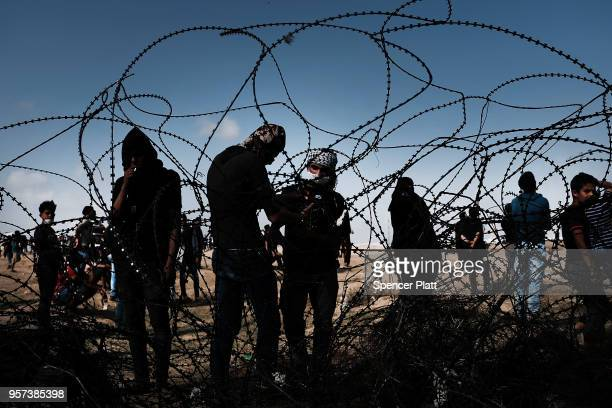 Palestinian youth pull away a section of the border fence with Israel as mass demonstrations at the fence continue on May 11 2018 in Gaza City Gaza...