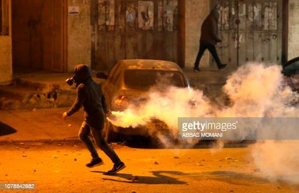Palestinian youth returns a gas canister lobbed by Israeli soldiers during an incursion into the West Bank city of Ramallah on January 7 2019