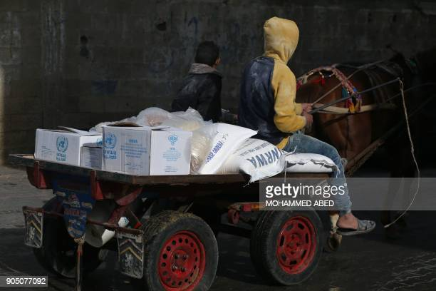 A Palestinian youth rides a horsepulled cart with food donations outside the United Nations food distribution centre in Gaza City on January 15 2018...