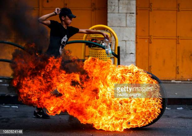 Palestinian youth runs past a rolling burning tire during clashes with Israeli forces following a demonstration after the weekly Friday prayers in...