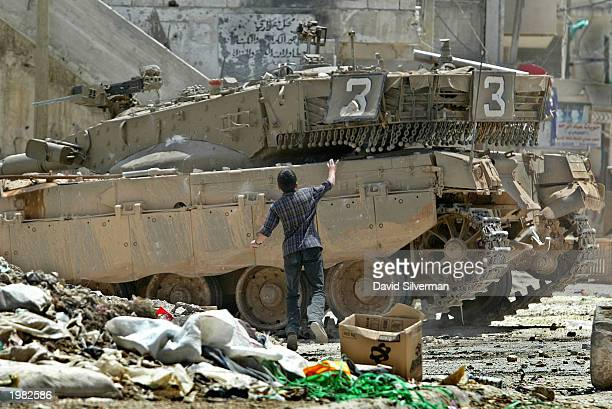 Palestinian youth runs right up to an Israeli army tank to throw stones at it during clashes with Israeli armored troops May 8 2003 in the Balata...