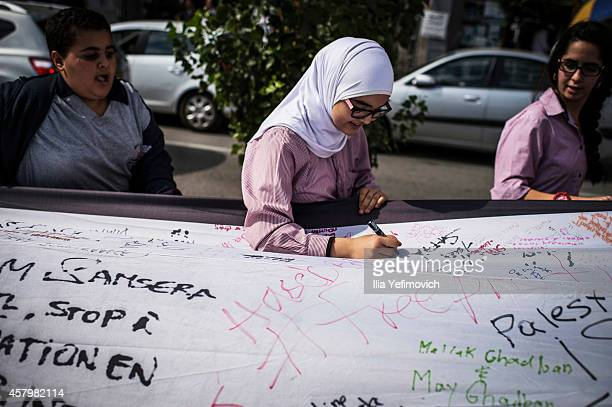 Palestinian youth seen writing in the centre of Ramallah with a 66 metre Palestinian flag symbolical of the 66 years since the establishment of the...