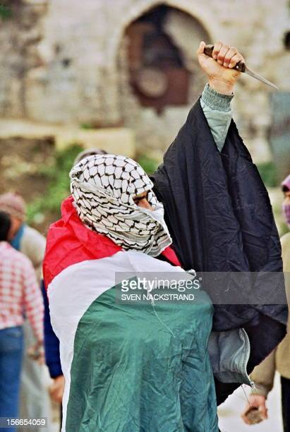 A Palestinian youth shown in a file photo dated 21 February 1988 with a Palestinian flag wrapped around him and a knife in his hand waiting for...