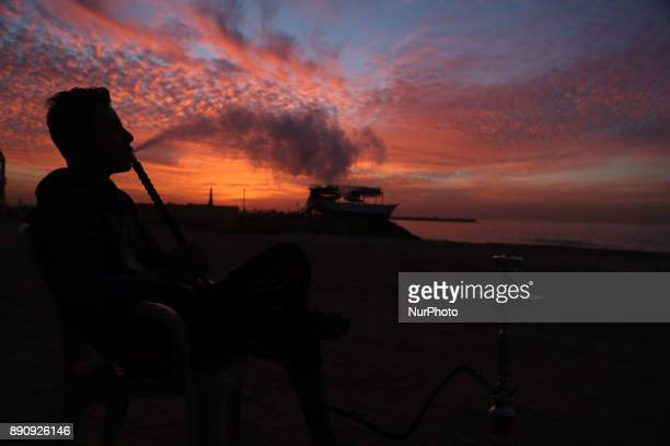 A Palestinian youth smoke waterpipe by the beach at sunset in Gaza CityDecember 12 2017